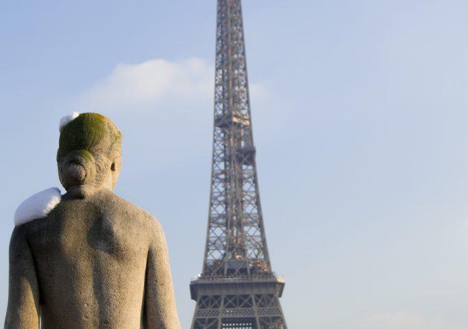Kip gole ženske od zadaj, v ozadju Eifflov stolp