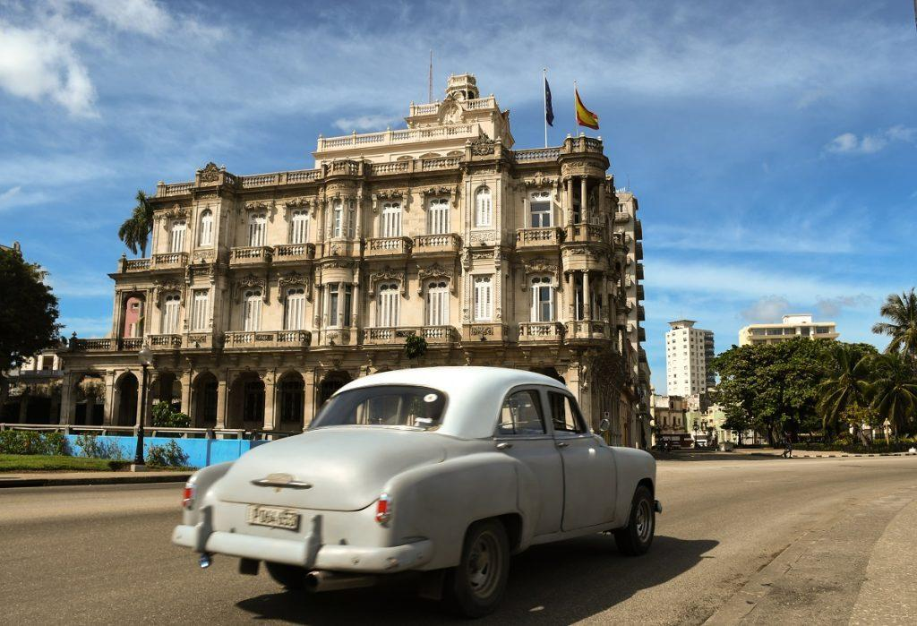 An old car in front of a colonial building in Havana