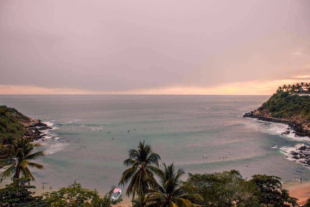 Zaliv s peščeno plažo in palmami. Na valovih majhne pikice - surferji