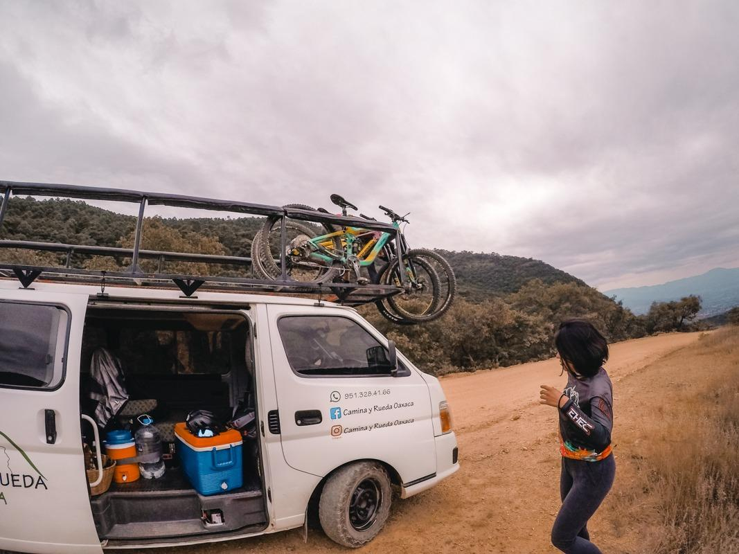 A white van with mountain bikes on top and a girl next to it (what to do in Oaxaca - go mountain biking!)