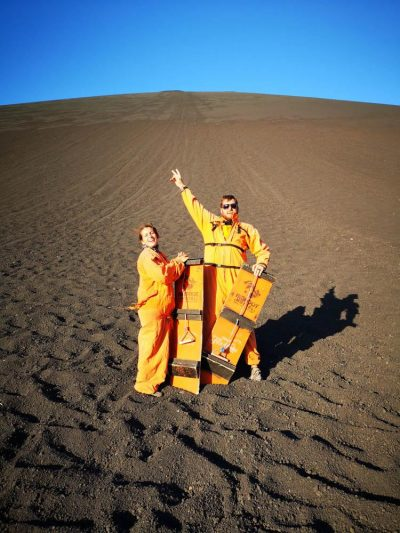 In orange onsies at the bottom of volcano (Volcano boarding in Leon, Nicaragua)