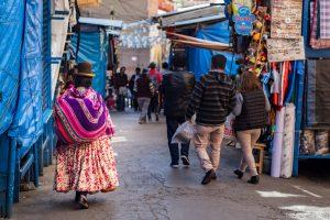 Potepuški nasveti za Bolivijo - naslovna slika-gospa na tržnici v tradicionalni opravi