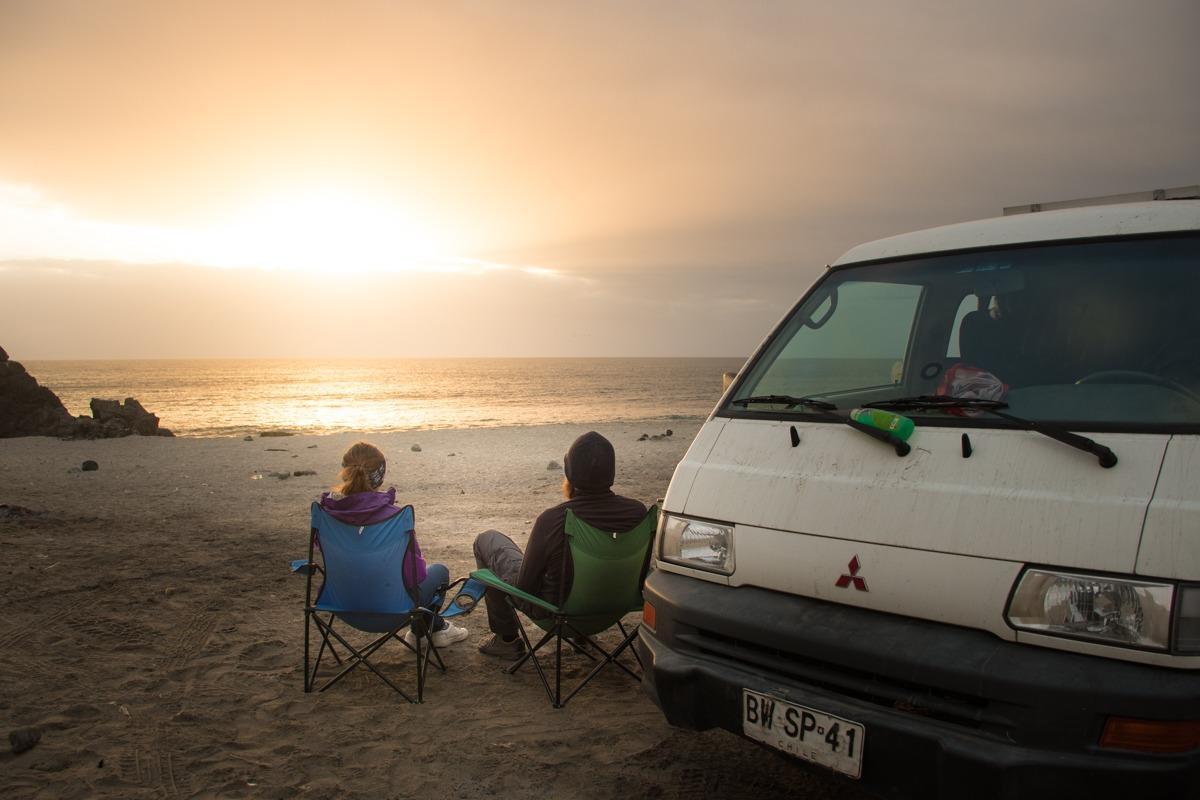 Dve osebi na stolčkih ob avtu, zazrti v morje. - nasveti za Čile