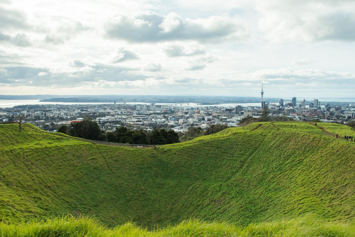 View from Mt Eden - grassy volcano crater and the city in the back. (cover photo of How to spend 3 days in Auckland)