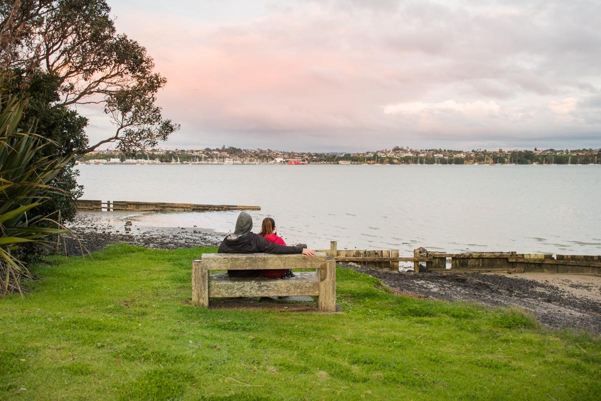 Us on a bank in Tahuna Torea Reserve, view over lagoon (How to spend 3 days in Auckland)
