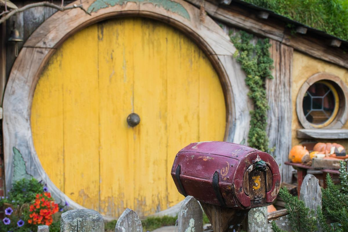 Wooden mailbox in a shape of barrel in front of the hobbit hole