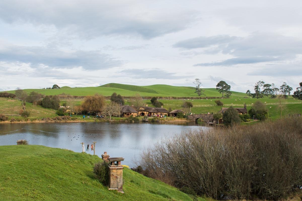 Pogled na gostilno pri Zelenem zmaju iz dežele Hobitov - jezero in hiška, mlin ter most v ozadju