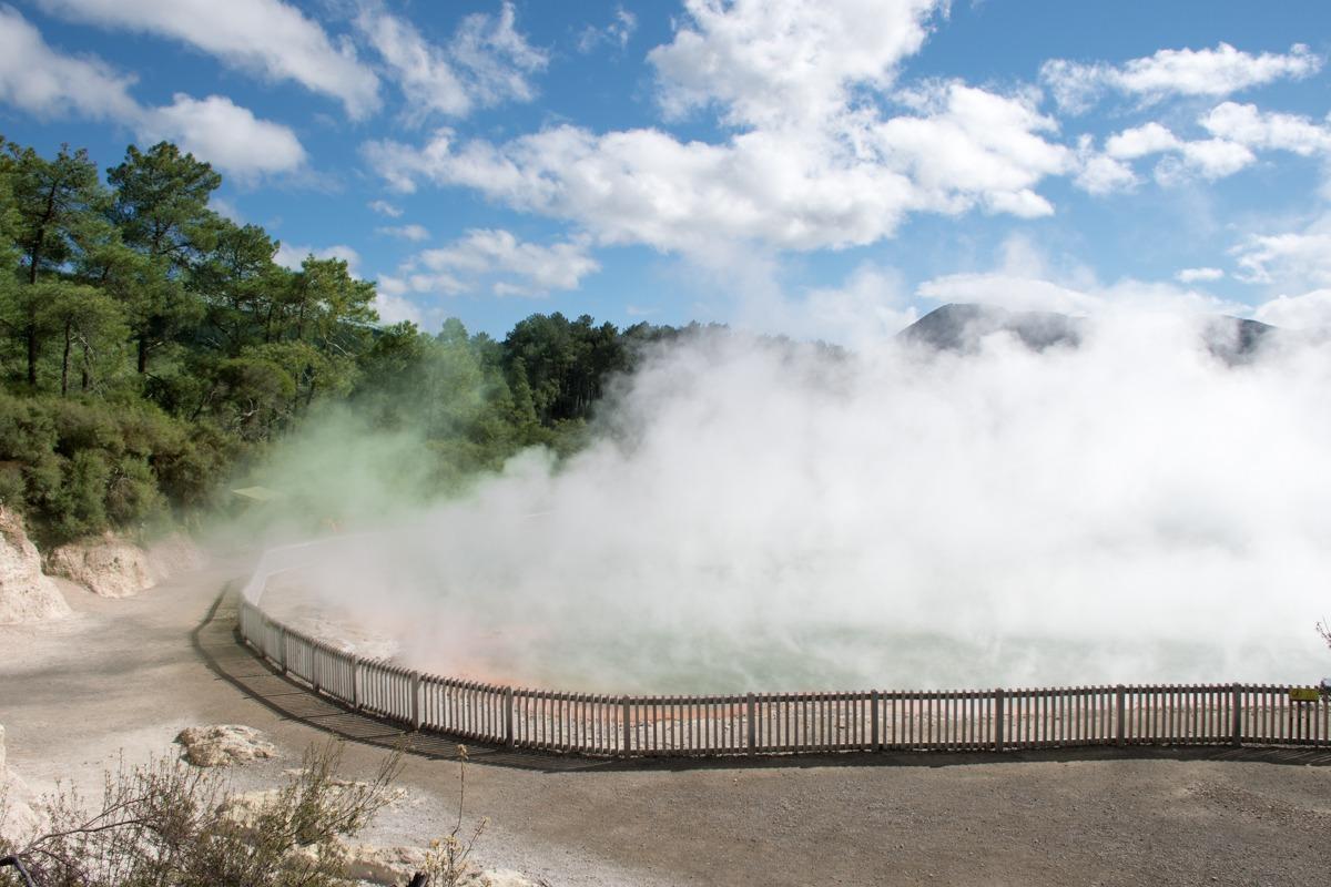 Dvigajoča se bela para iz velikega termalnega vrelca v geotermalnem parku (prispevek na temo Stroški potovanja za Novo Zelandijo)