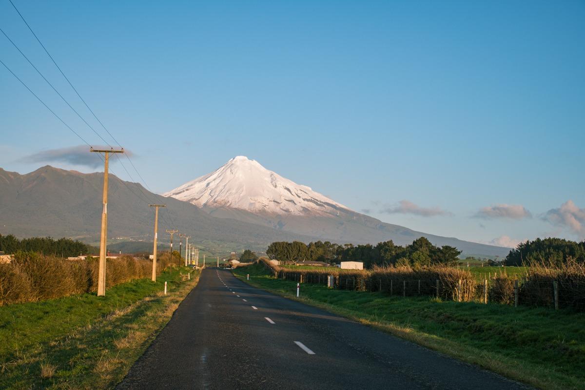 Cesta, ki vodi v smeri stožčastega vulkana, katerega vrh je pokrit s snegom