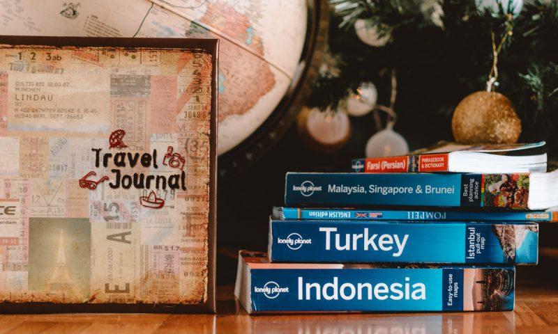 Lonely planeti, popotniški dnevnik ter globus pod božično jelko (Božična darila za popotnike naslovna fotka)