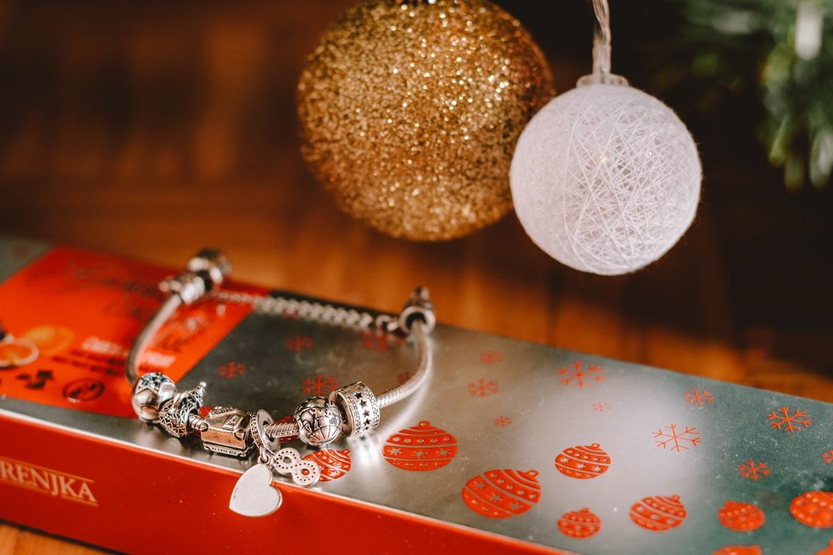 A close up photo of Pandora bracelet with travel inspired charms under Christmas tree (Christmas gifts for travelers)