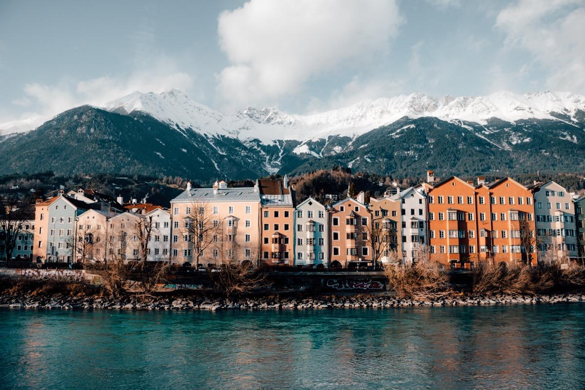 Barvite hišice Innsbrucka v vrsti ob reki, zadaj zasneženi hribi