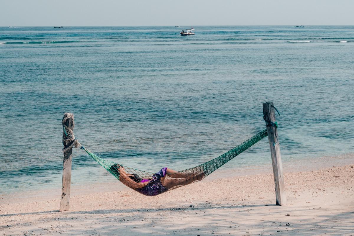 V viseči mreži na peščeni plaži ob oceanu - prispodoba rajskega otočka