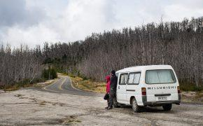 How to buy a car in Chile as a foreginer cover photo (a couple and a white van on a road. Burnt forest around. )