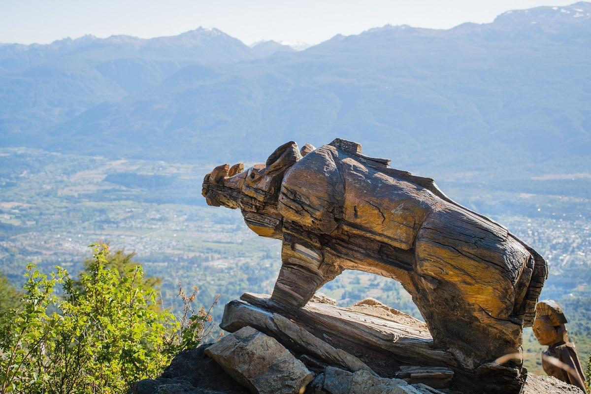 A wild pig carved from wood overlooking town