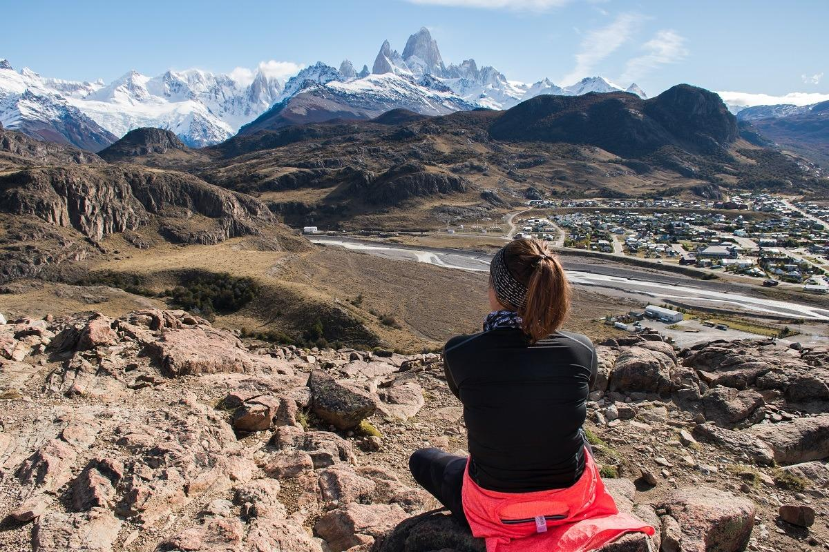 A sunny day in El Chalten, Argetina, Sandra showing back, mountain range in the distance.