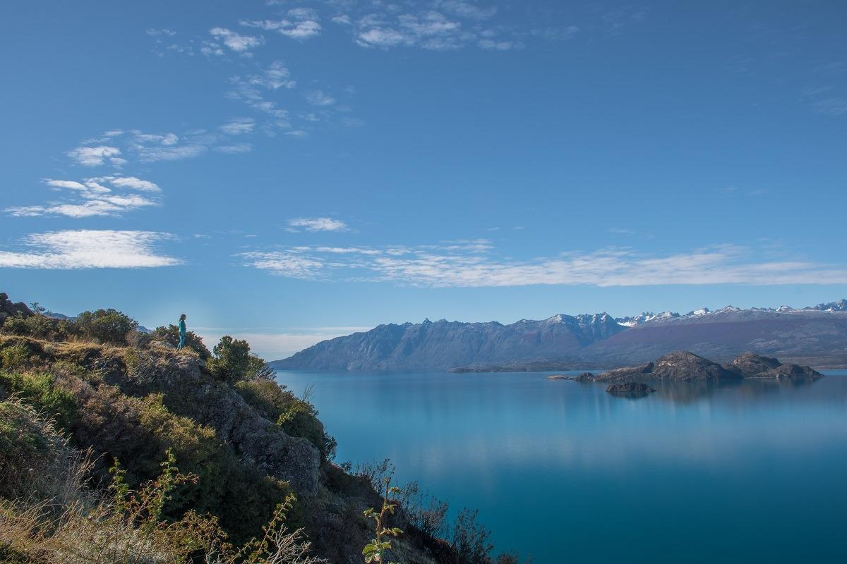 A blue lake in Chile, a girl in the distance, looking at it. A mountain range in the distance.