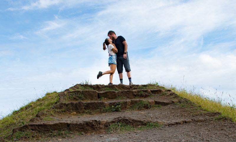 Our yearlong honeymoon cover photo - a couple kissing on the top of hill
