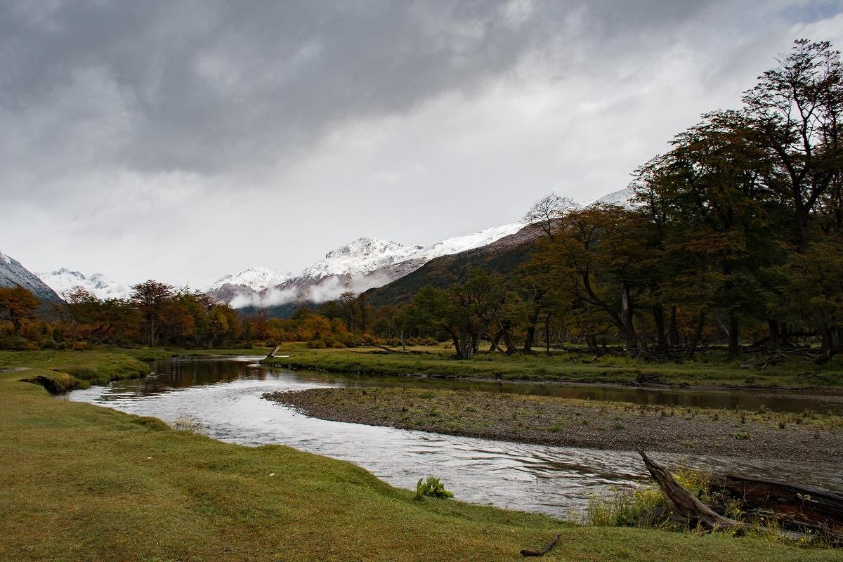 Hiking in Ushuiai cover photo - the river, muddy meadow and snowy mountains in the distance