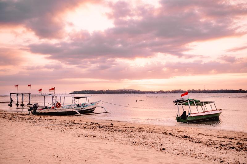 Sončni zahod na Gili Air - čolna ob obali in roza obarvano nebo