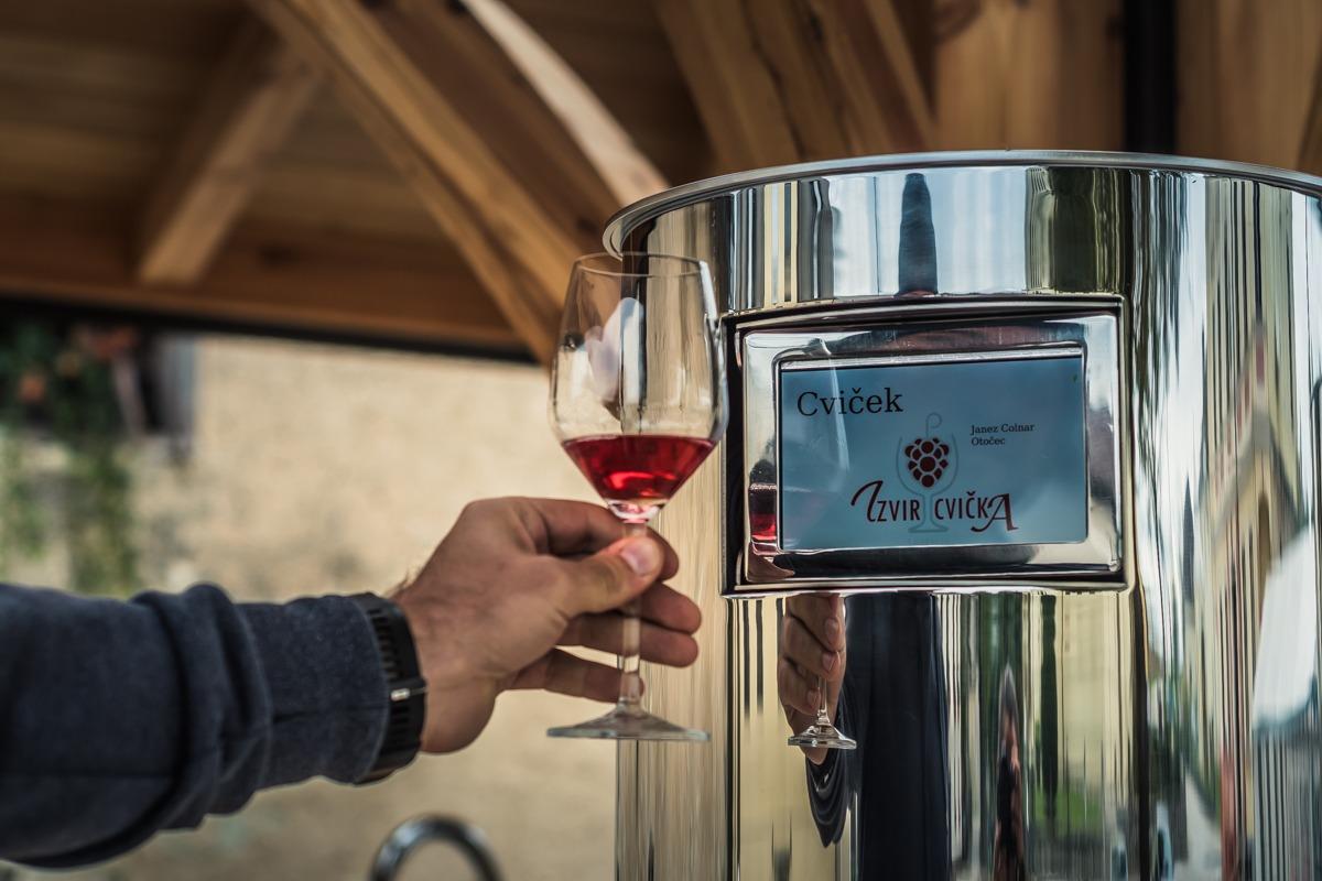 Izvir Cvička in kozarec s cvičkom - ena izmed znamenitosti Dolenjske